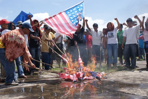 As culmination of the three-day Bicol Anti-VFA Caravan, protesters symbolically burn 25 US flags to signify defiance against US military intervention and aggression.